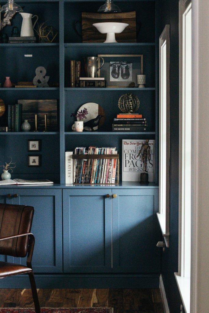 Blue bookcase against silky, dark walls