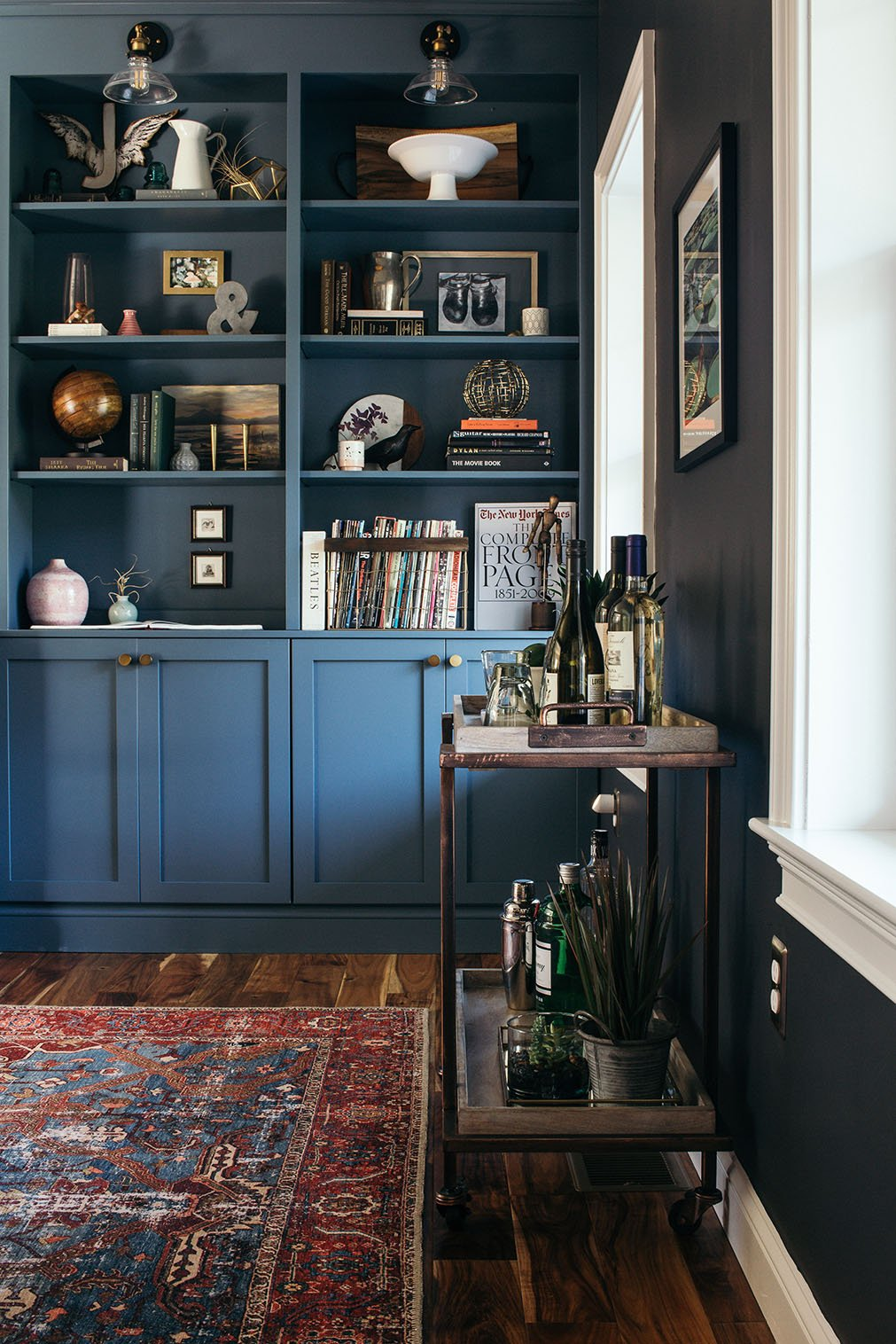 Blue built-in bookcase with bar cart in a moody library