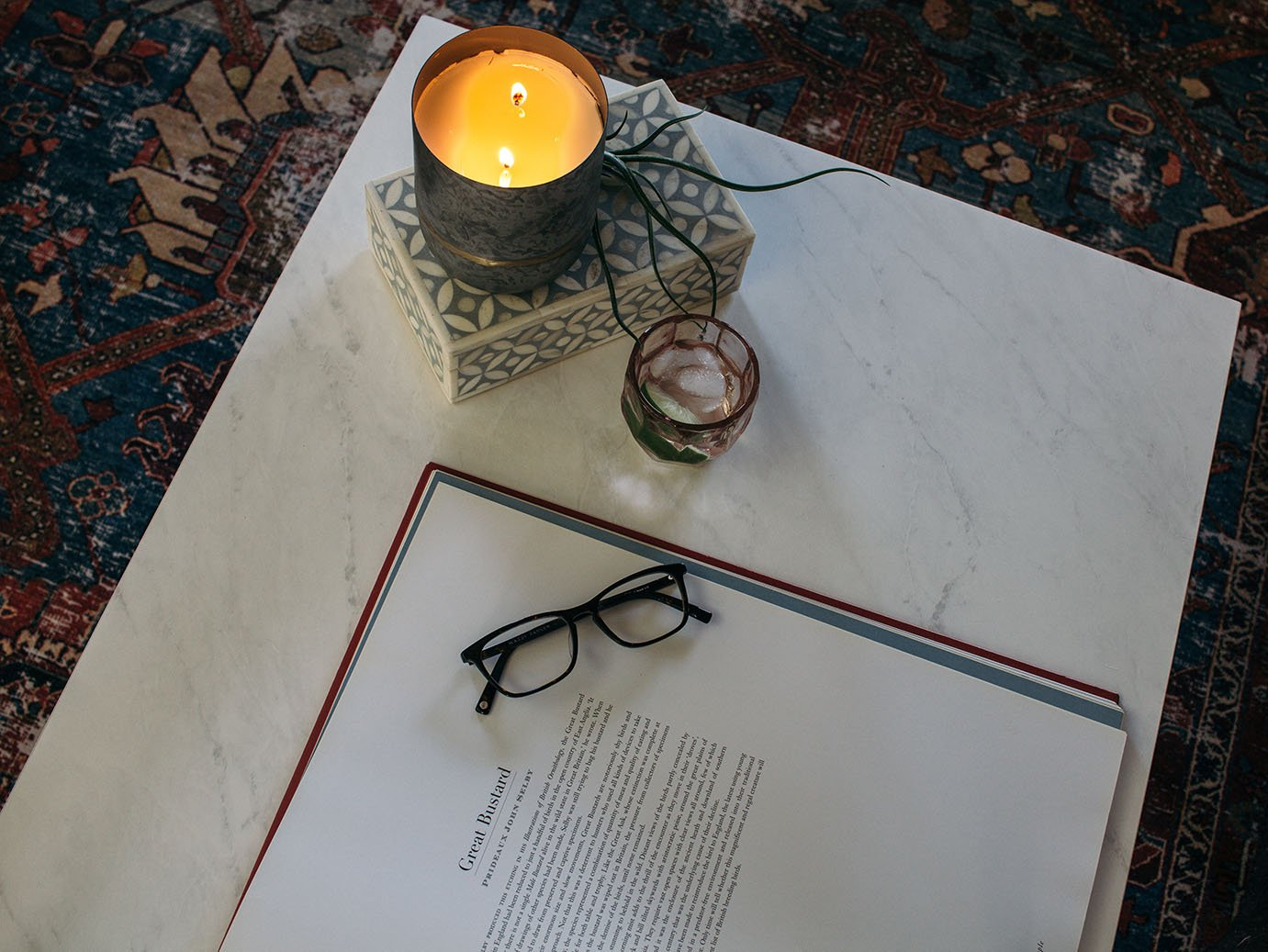 Marble coffee table on topof a vintage rug with a candle, book, and glasses.