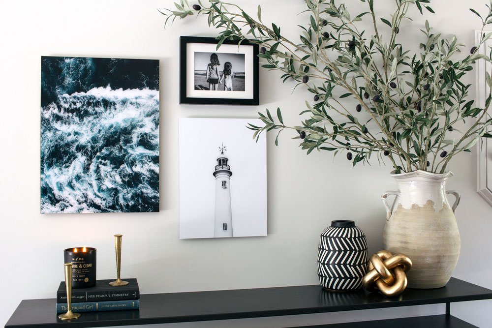Olive branches on a modern entryway table with coastal artwork