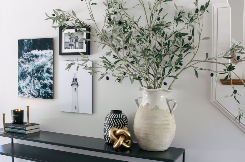 Olive branches in pottery with coastal artwork