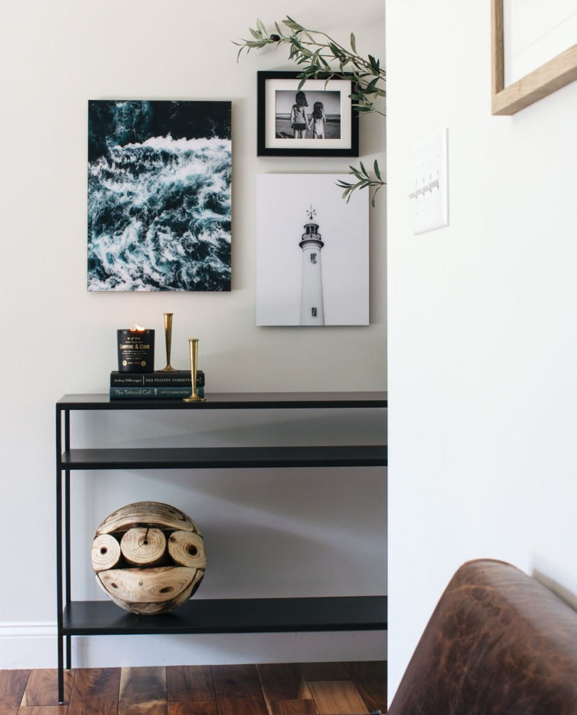 Modern entryway with coastal inspired art and a black console table.