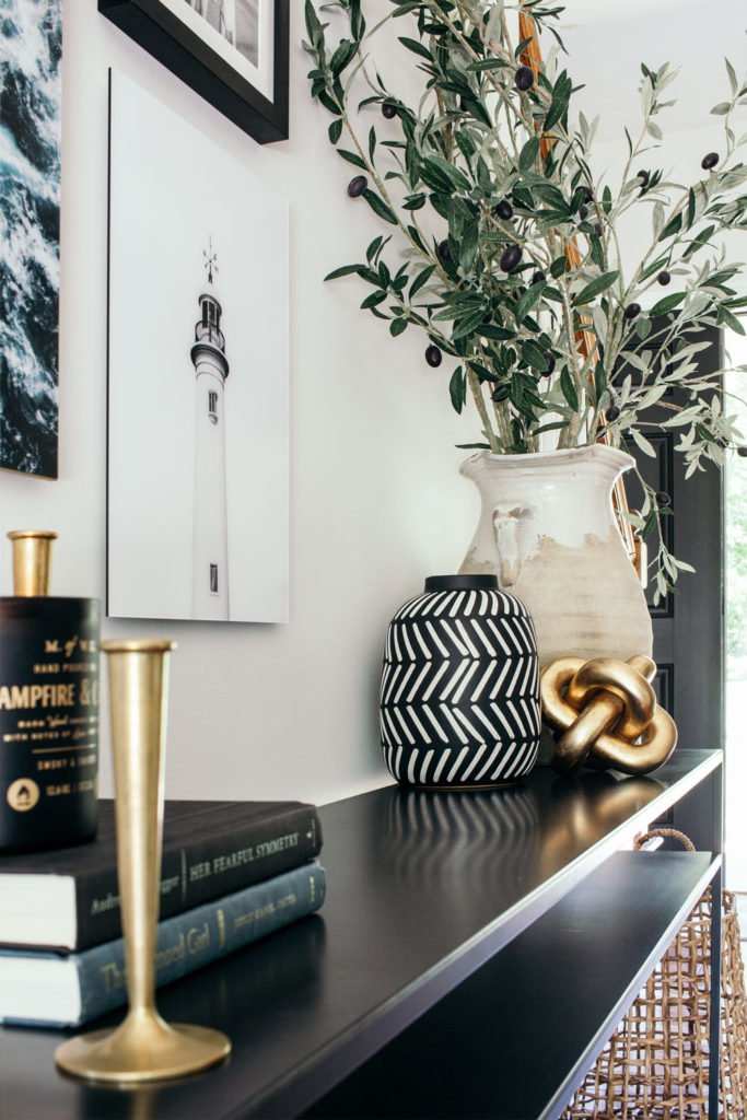 styled entryway with narrow console table, brass candlesticks, olive branches and coastal artwork