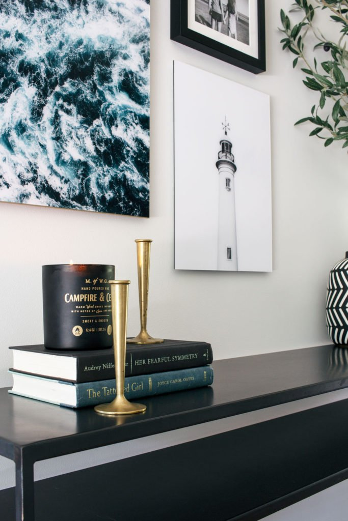 Brass candlesticks on a black console table in the entryway