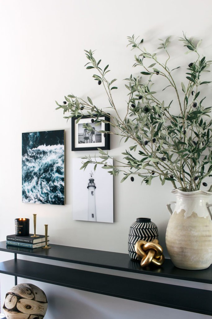 Olive branches in pottery on a black console table in a modern entryway