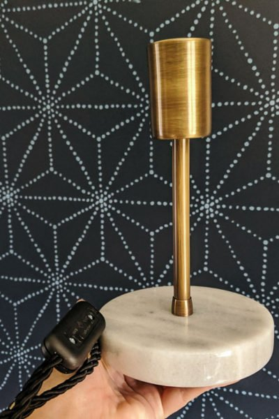 This brass and marble lamp is perfect against the blue stenciled accent wall.