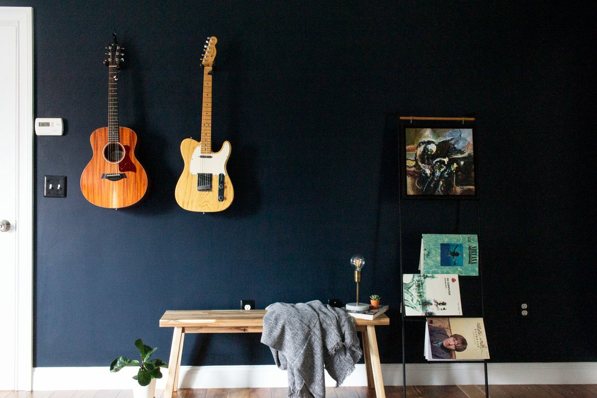 The guitar wall feature of this dark and moody master bedroom is beautiful and functional.