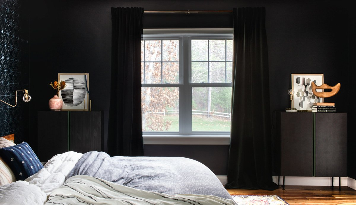 Black and green dressers flank the bedroom window