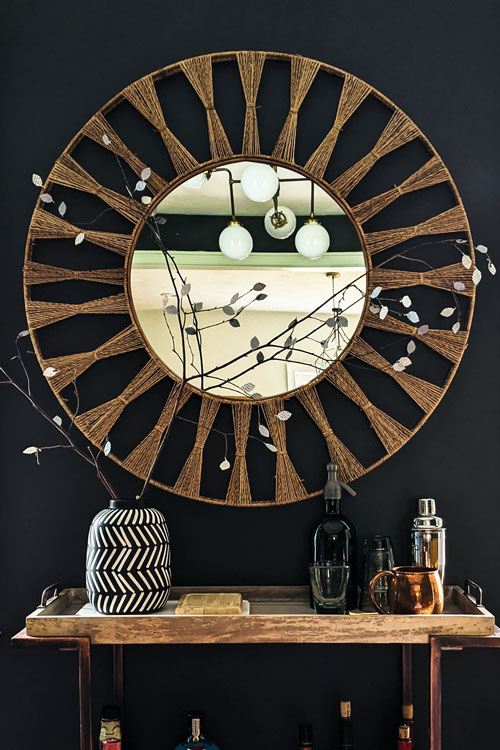 Large round statement mirror over styled bar cart makes for a gorgeous decor moment.