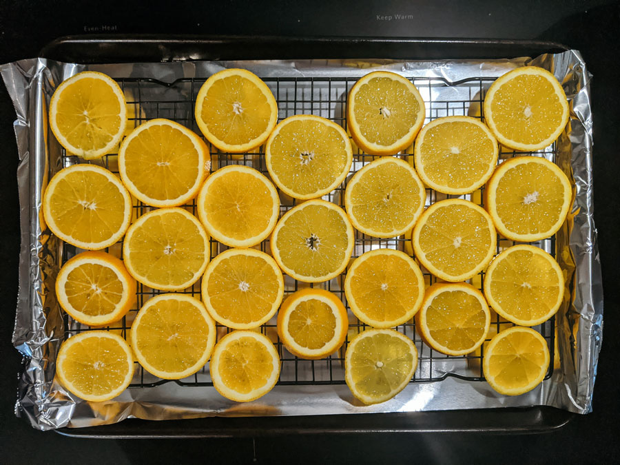 bake orange slices at 200 degrees for 4 - 6 hours, flipping every 30 minutes