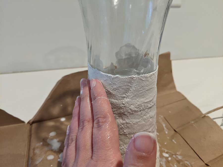 smooth plaster cloth onto vase