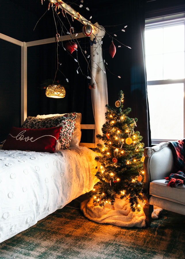 Little Christmas tree with orange slices, candy canes, and twinkle lights next to a bed.
