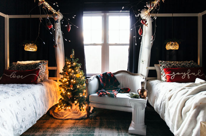 Tween girls bedroom decorated for Christmas with dried oranges, winter branches, plaid, and holiday bedding.