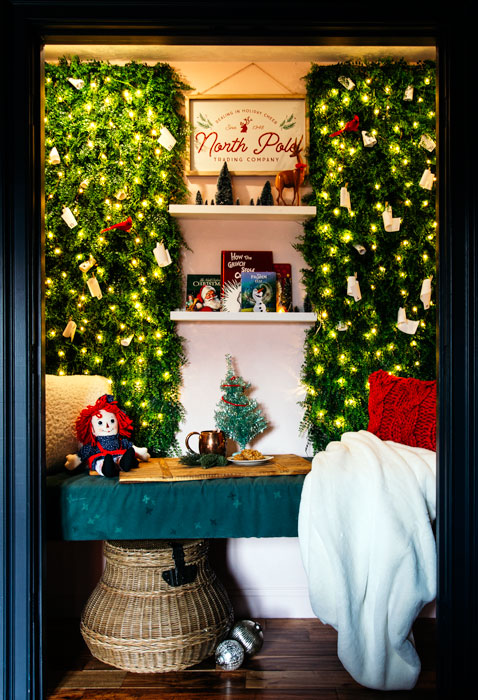 Whimsical reading nook decked out for Christmas. Raggedy Ann is enjoying a cup of hot cocoa while admiring the twinkle lights under the easy DIY advent calendar.