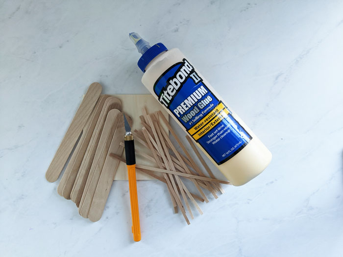 Gather your materials: craft sticks, wood glue, coffee stir sticks, and a wood square