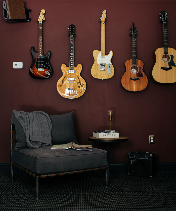 Here's our small man cave on a budget, featuring a music corner with hanging guitars on a dark red wall.