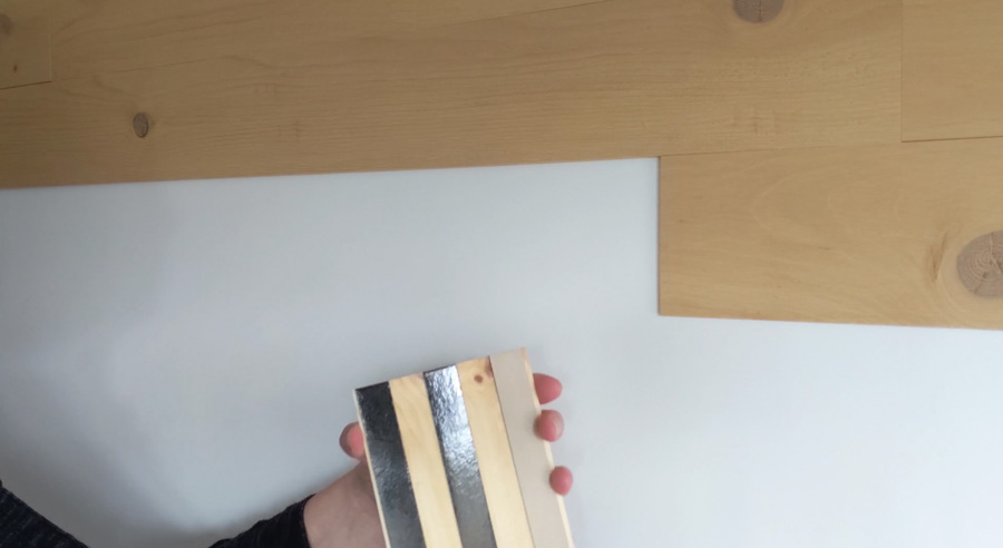 Peel backing from adhesive on back of wood planks