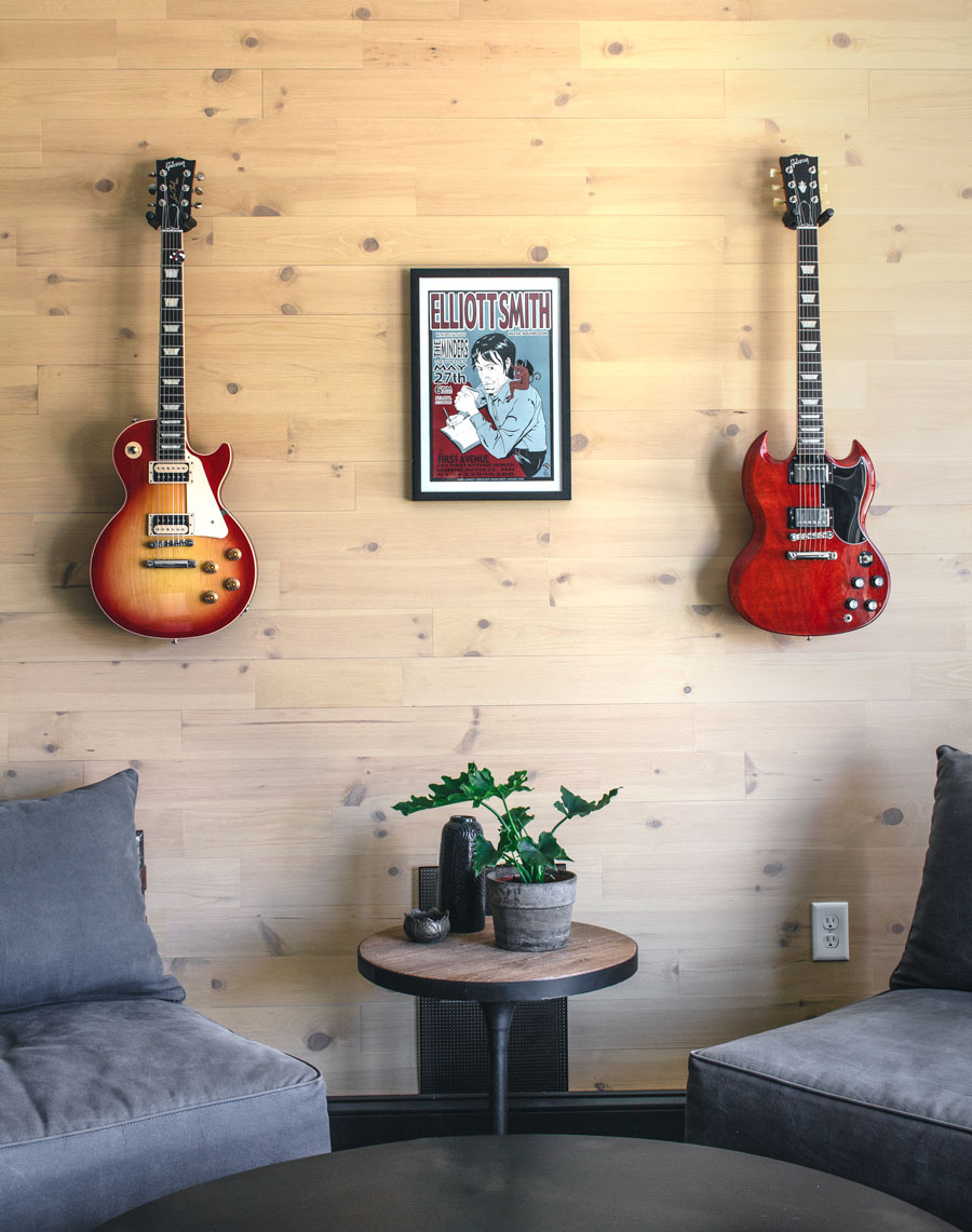 Sitting area against reclaimed peel and stick wood wall with guitars and Elliot Smith poster.
