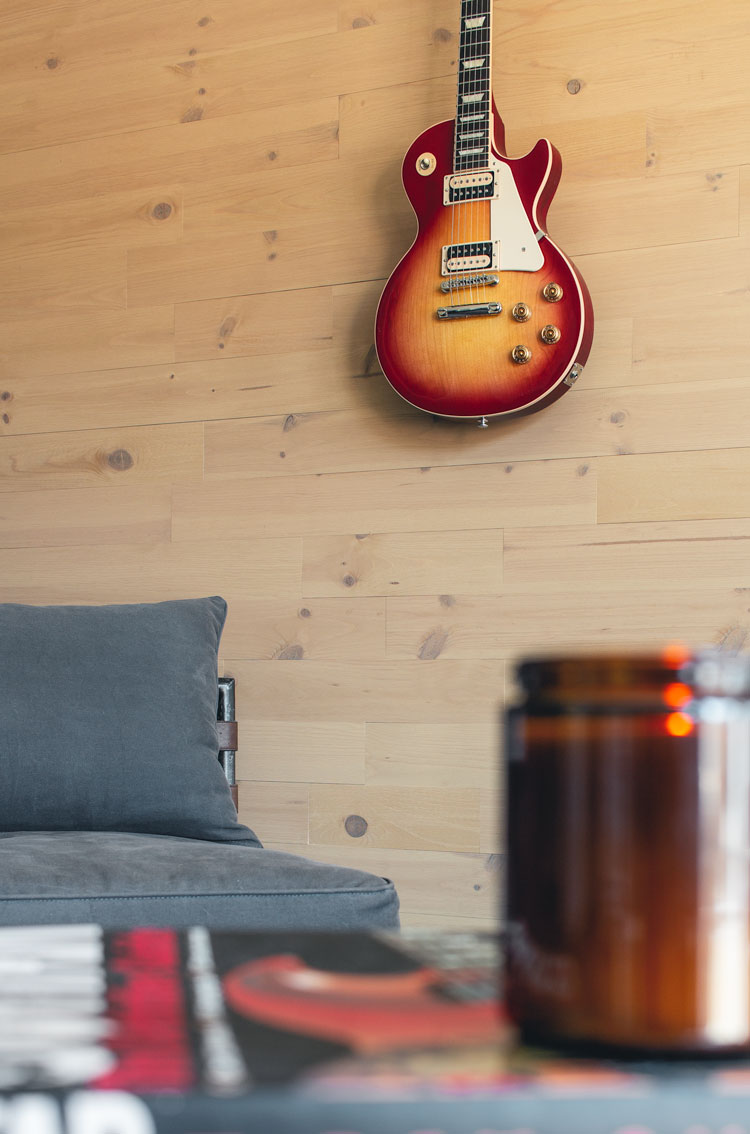 Reclaimed wood wall with guitar and candle in foreground