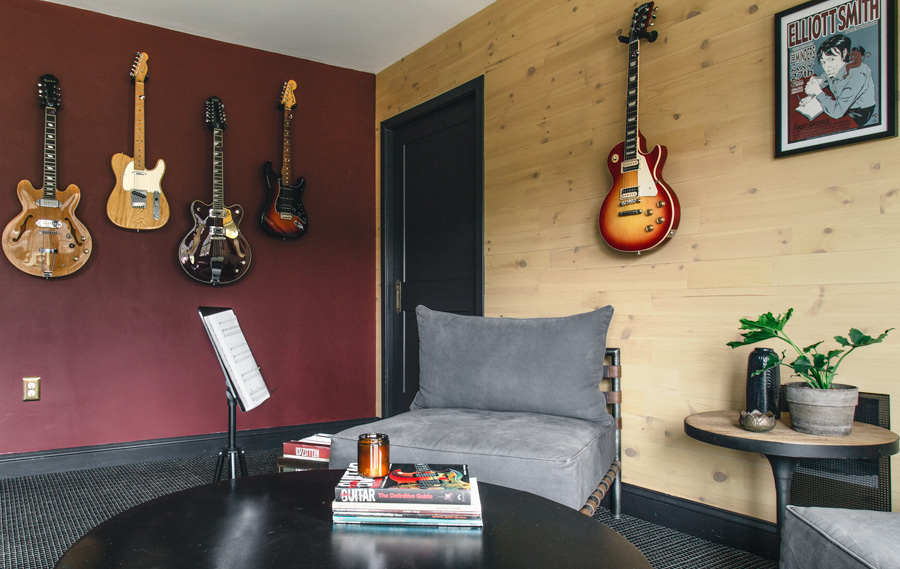 Dark red wall with reclaimed wood wall and hanging guitars in basement music room.