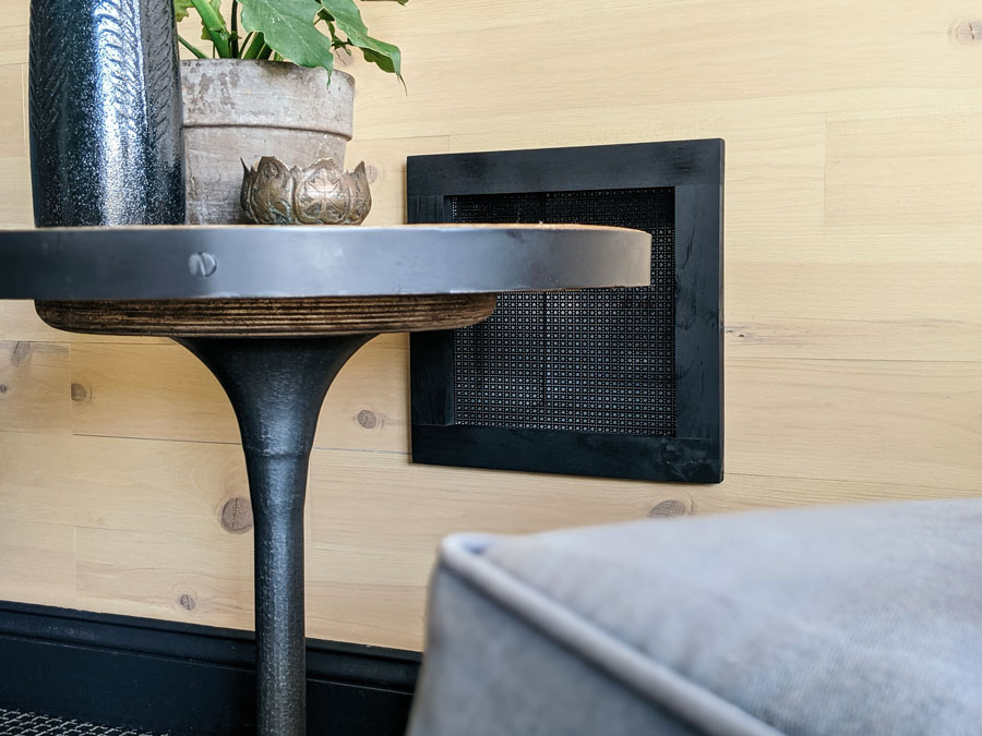 DIY decorative air vent cover installed in a room on a wood wall behind an industrial tulip table