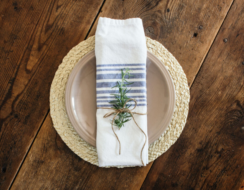 Seagrass placemat with blue and white napkin makes a high-end coastal decor table setting