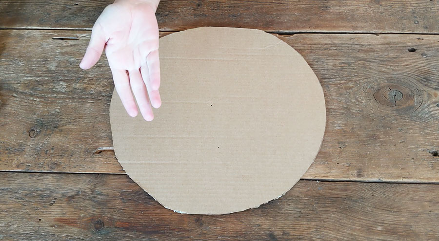 Cut out a circle of cardboard from an old box to use as the base for your braided grass placemat.