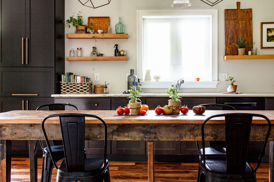 Kitchen with black cabinets and marble countertops decorated for summer. Tomatoes and basil on vintage wood table. Open shelving.