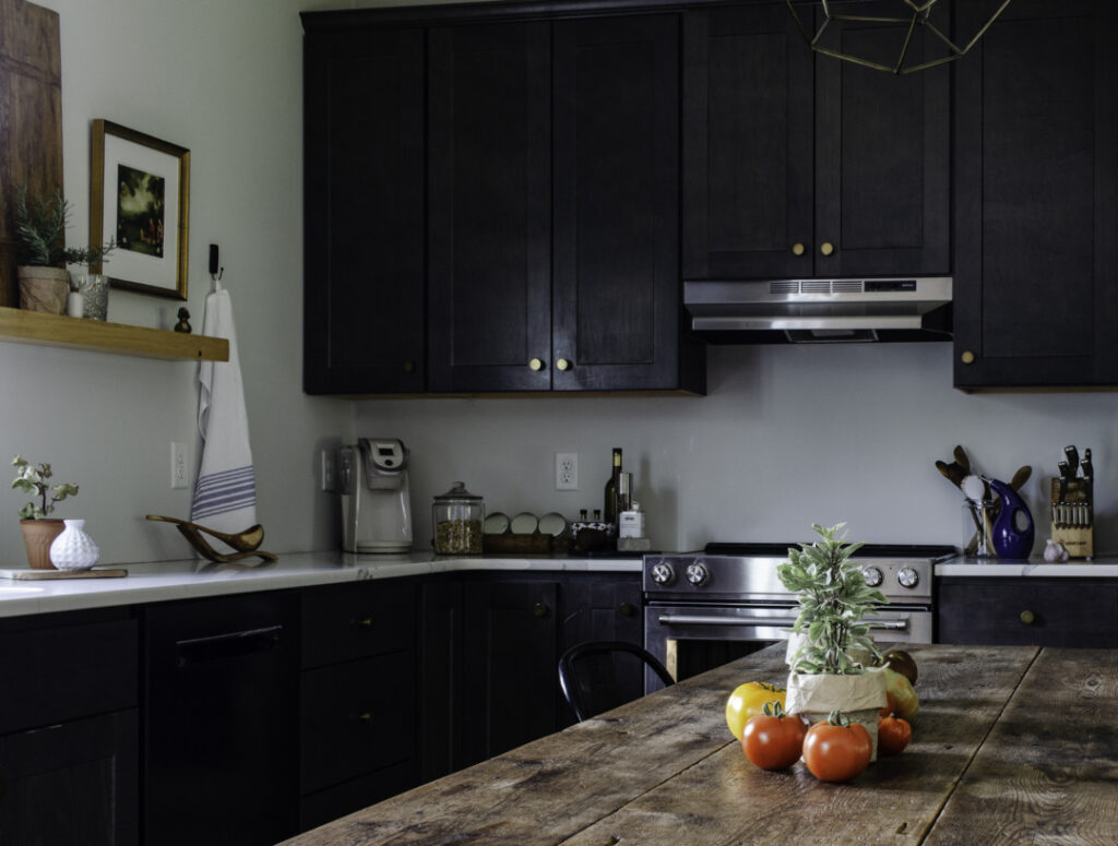 Kitchen with black cabinets, marble counters, and open shelving, decorated for summer. Heirloom tomatoes and potted basil on a vintage table.
