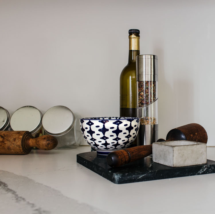 Blue and white bowls on soapstone tray with bottles of olive oil.