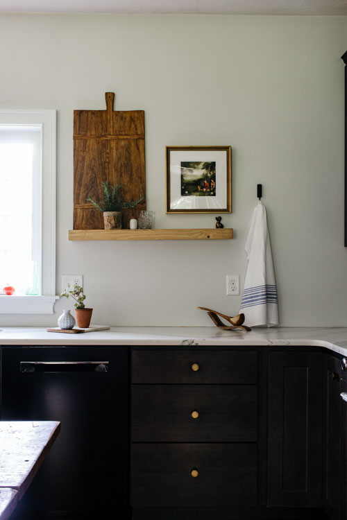 Open shelf in kitchen with black cabinets and marble countertops. Vintage breadboard and artwork finish off the kitchen styling.