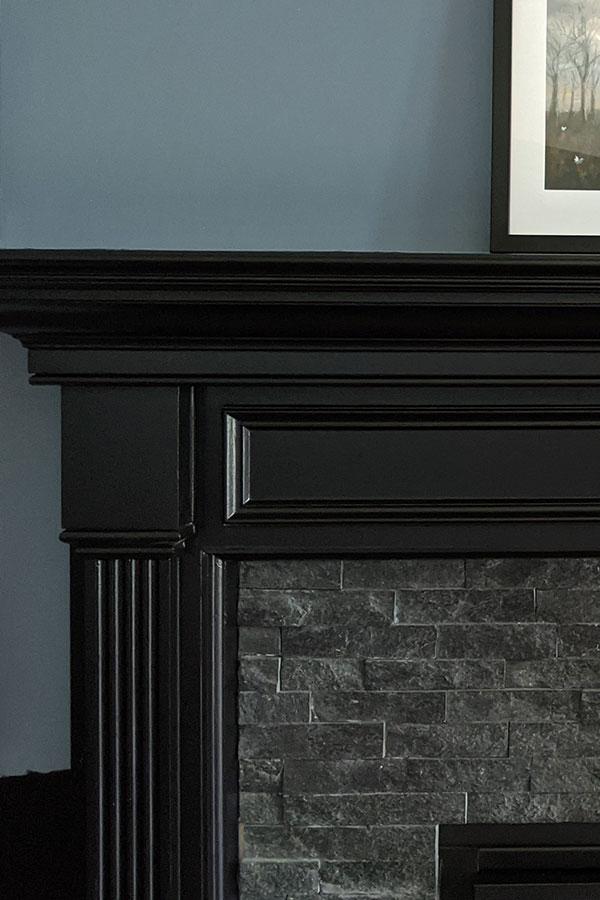 Black fireplace on a blue wall