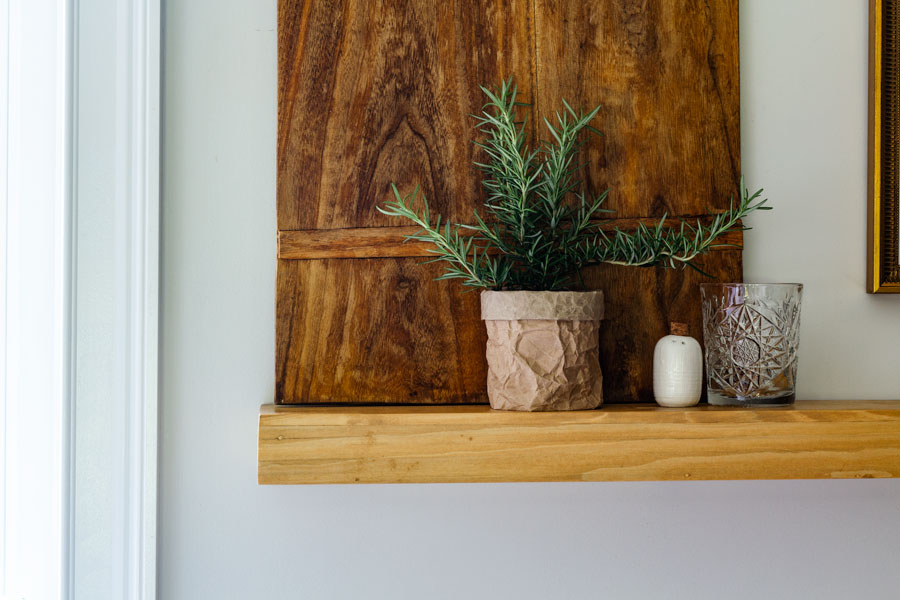 Rosemary plant on open shelving in front of vintage breadboard.