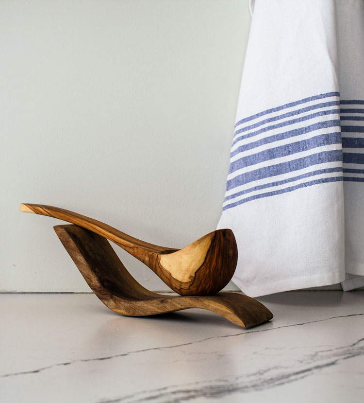Blue and white striped dish towel with olive wood serving spoon.