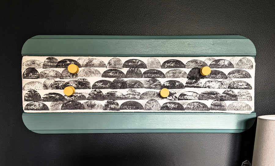 Completed DIY fabric covered bulletin board. This easy DIY craft is a good way to make a pinboard without using cork.