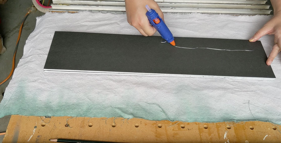 wrap your pinboard in fabric and attach using hot glue