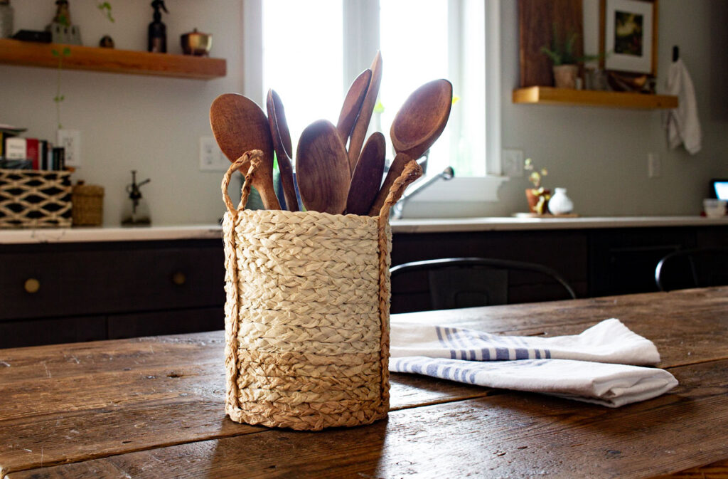 Here's the finished ombre basket with handles holding a set of vintage wooden spoons on a rustic wood table in the kitchen.
